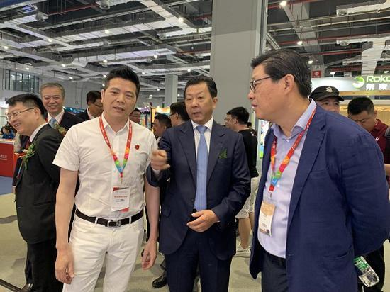 图为:艾力斯特总裁周国海陪同国家体育总局副局长李颖川参观艾力斯特品牌展馆